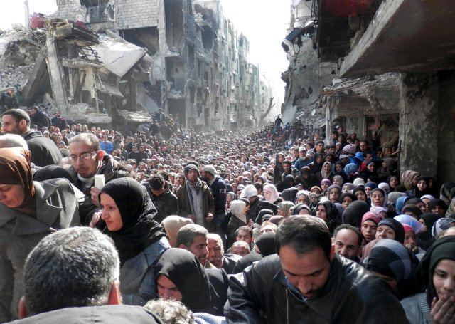 Palestinian refugees in Syria wait for food assistance.